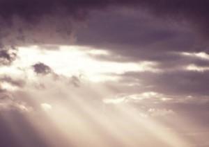 Sunbeams shining through a stormy grey sky